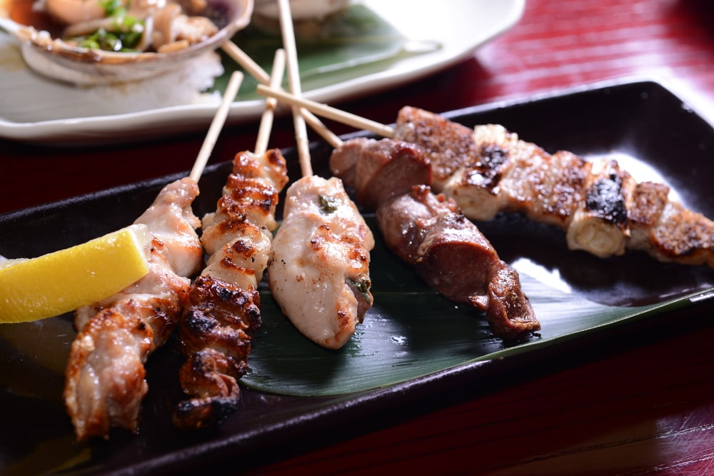 Plate of Japanese style grilled meats on skewers
